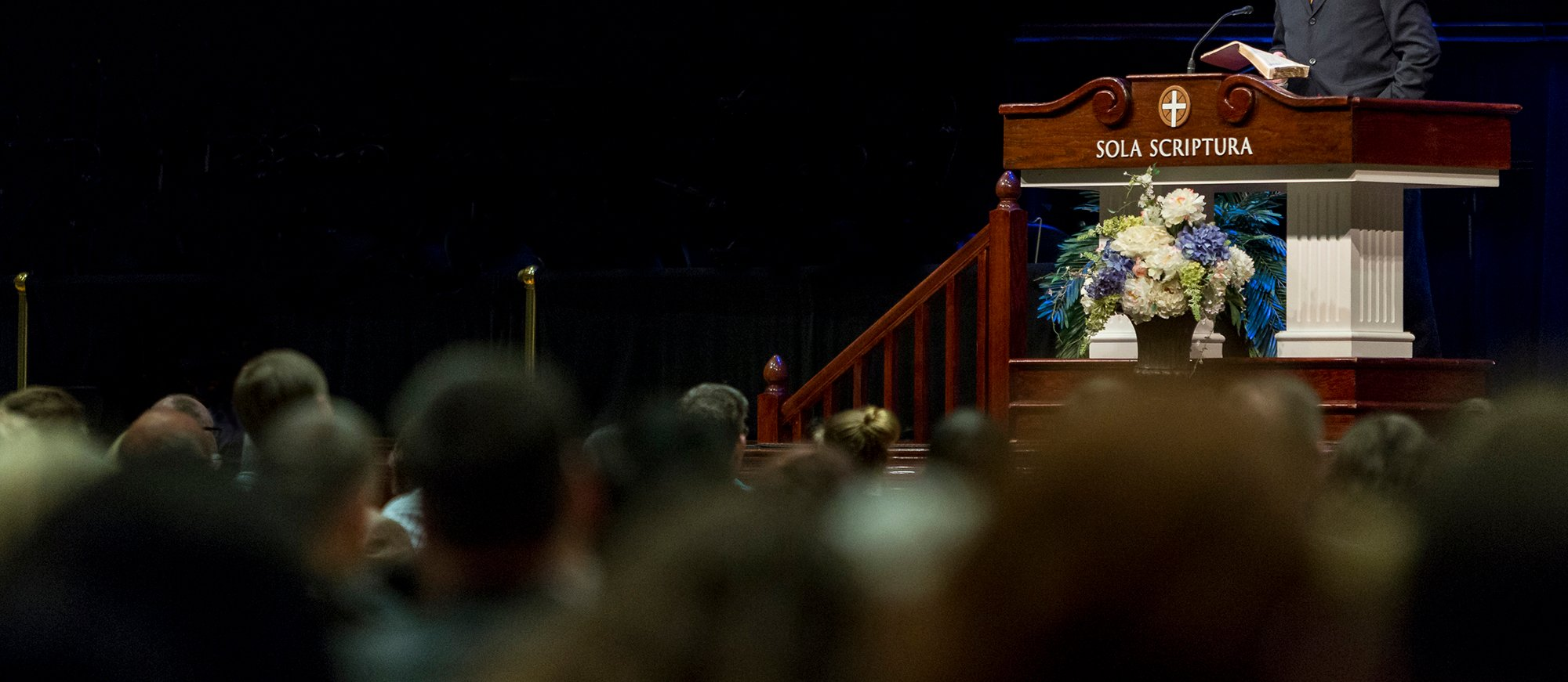 Church pulpit with sola scriptura inscribed and pastor preaching to conference